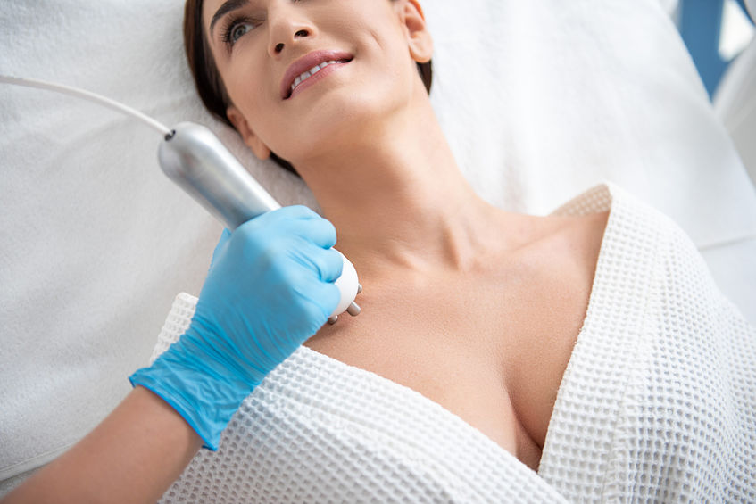 Woman in medispa receiving treatment to decolletage